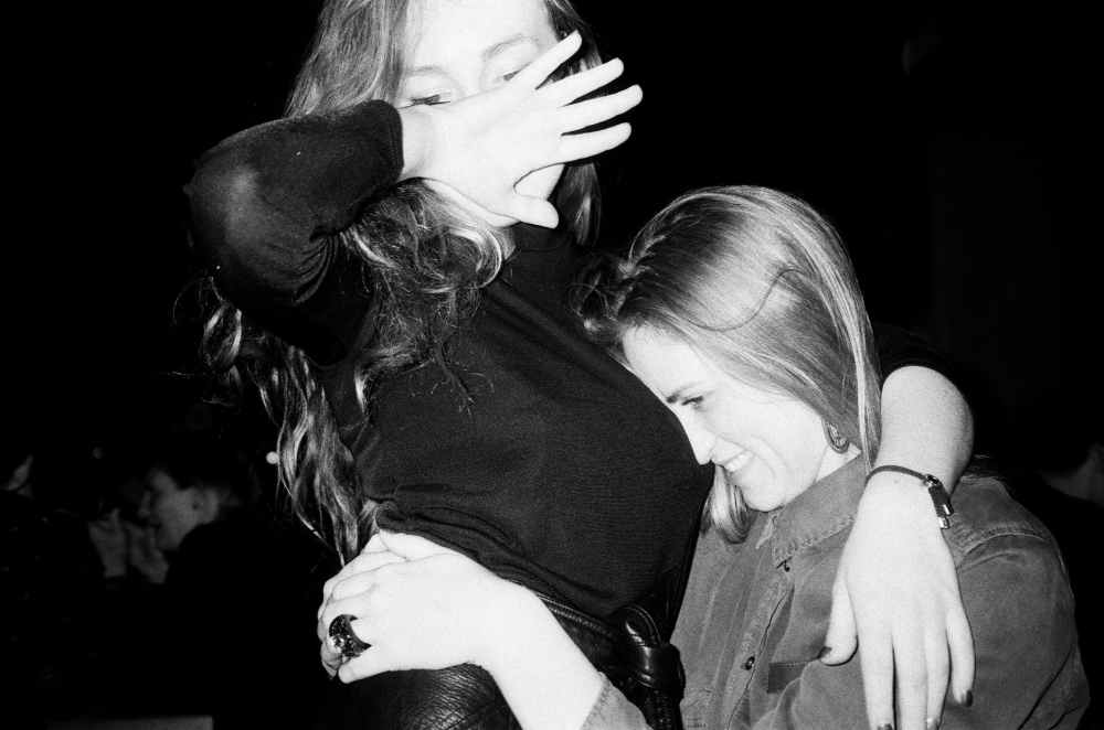 grayscale photo of woman hugging woman in black long sleeved shirt